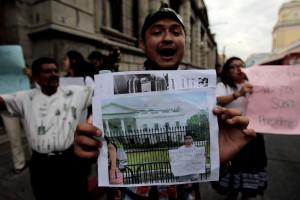 Una manifestante en Ciudad de Guatemala enseña la foto de un amigo suyo que apoya la protesta contra la corrupción desde Washington. EFE